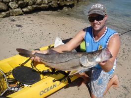 man holds up catch from kayak fishing in Costa Rica