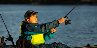 A boy casts his kids fishing rod from an Ocean Kayak outfitted with fishing gear