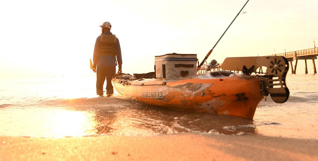 man launching an Ocean Kayak Trident 13 fishing kayak from beach at dawn