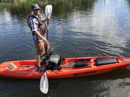 Man stands with paddle on top of the Bonafide SS127 fishing kayak