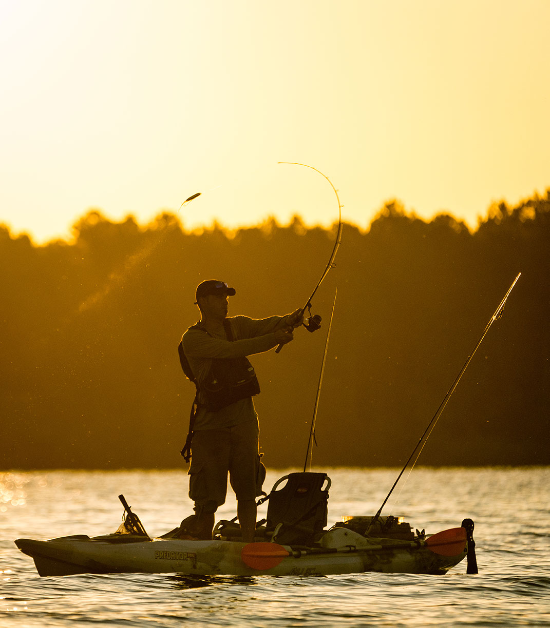 man casts a lure from a fishing kayak in golden morning light in Charleston, South Carolina