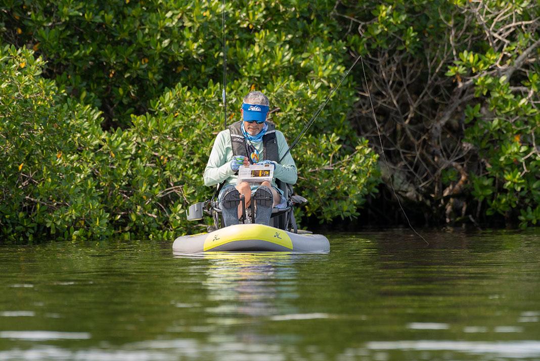 Man fishes on a Hobie Mirage iTrek 9 inflatable kayak