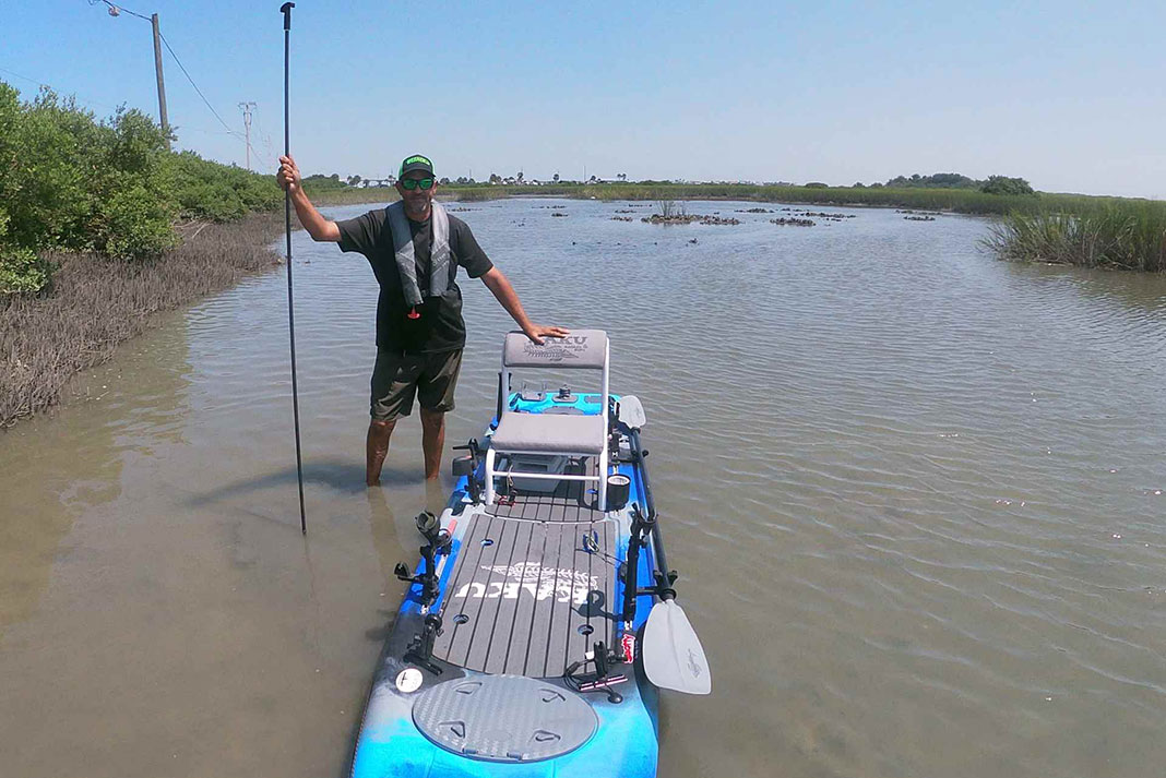 man stands beside kayak in shallow water holding a stakeout pole