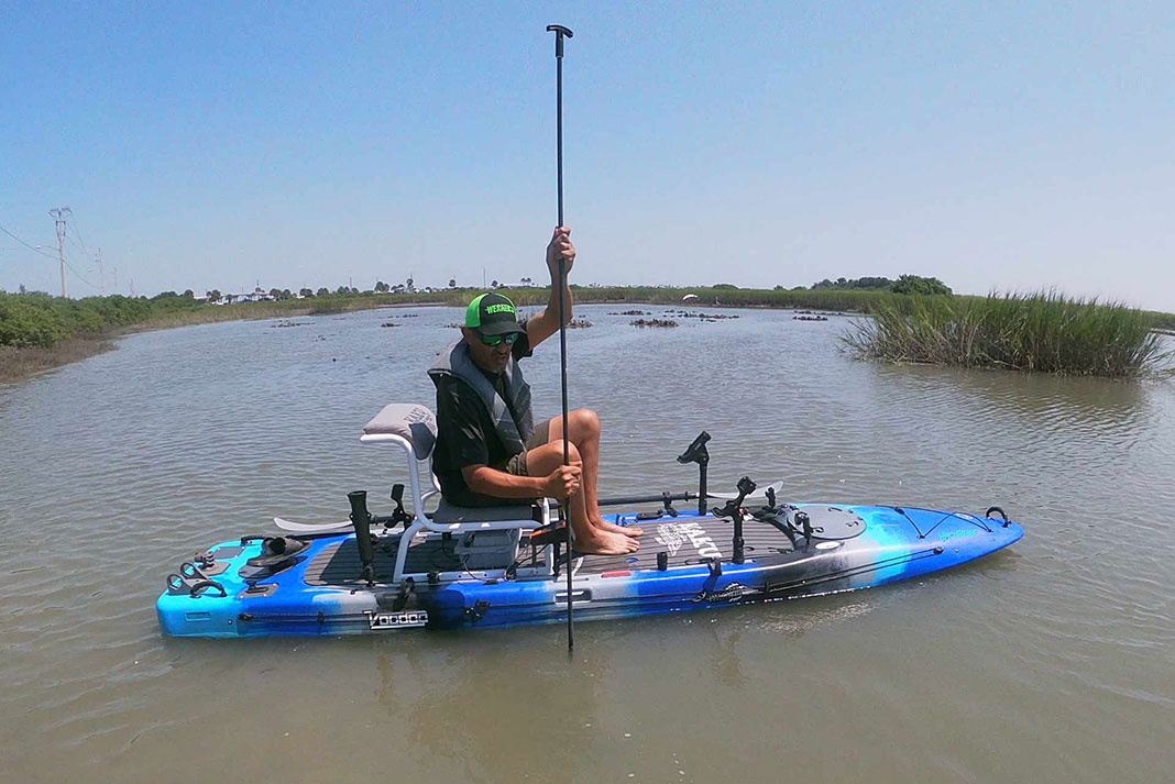Man uses stakeout pole as depth finder from his fishing kayak