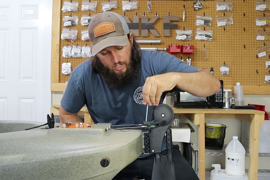 man installs a new rudder bolt on the Salty PDL kayak