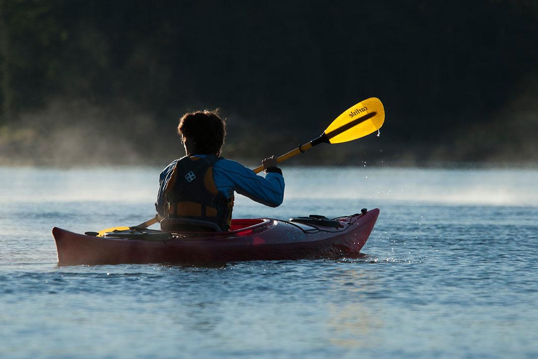 Person paddling an Old Town kayak using a Carlisle Paddle