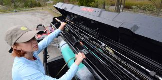 angler loading her fishing rods into storage rack on her truck