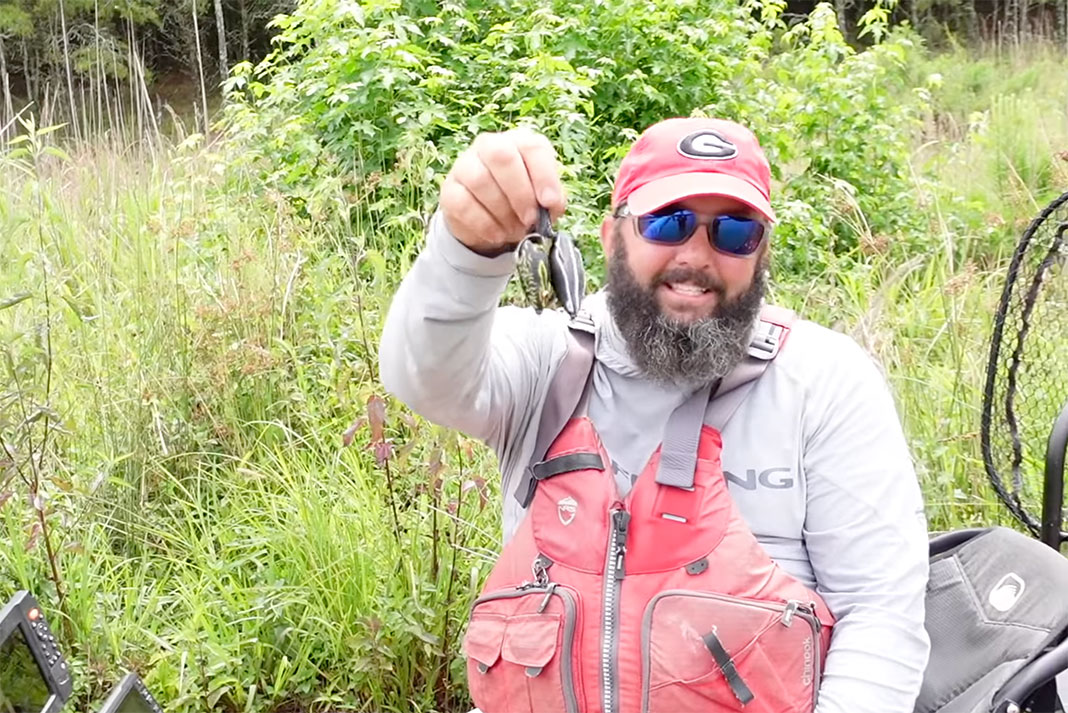 Gene Jensen holds up two hollow body frog lures for bass fishing