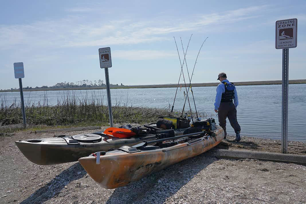 Angler loads his kayak tackle storage crate before launching in the ocean
