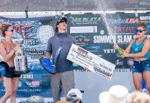 man celebrates victory on podium at a 2021 kayak fishing tournament