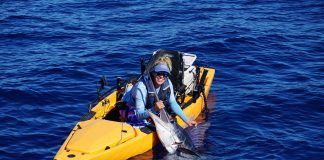 Bri Andrassy holds up the striped marlin she caught by kayak