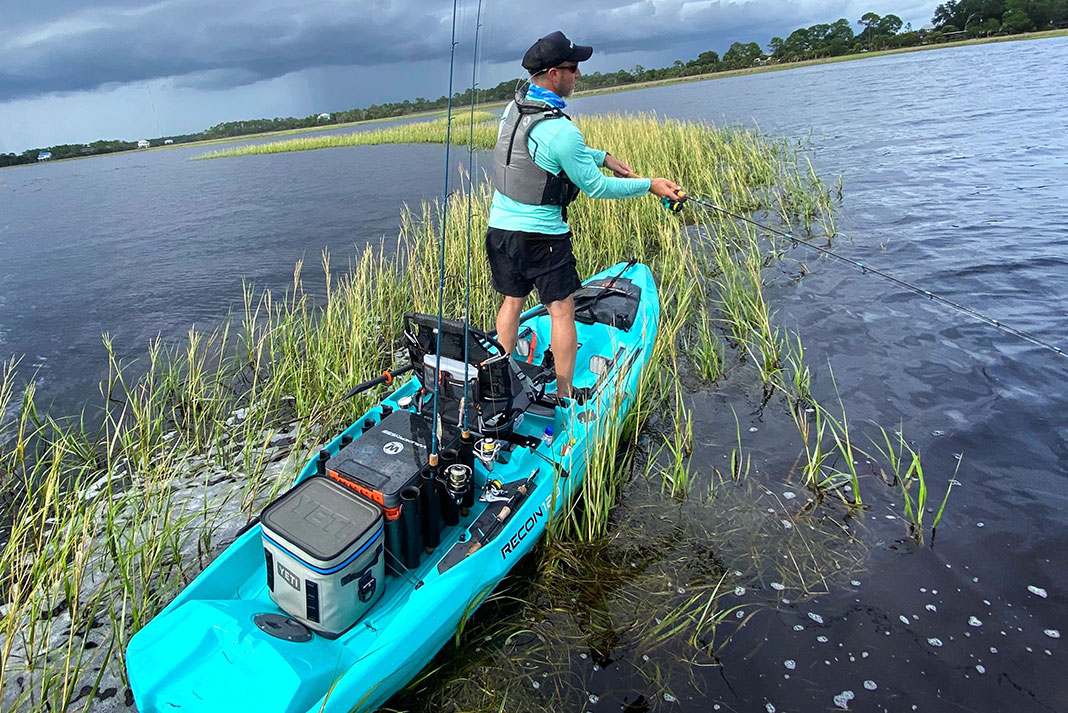 Angler fishes from a Wilderness Systems Recon kayak with a Yeti cooler in the back