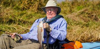 Mike LaFleur holds up a fish, an example of the benefits of fishing for older anglers
