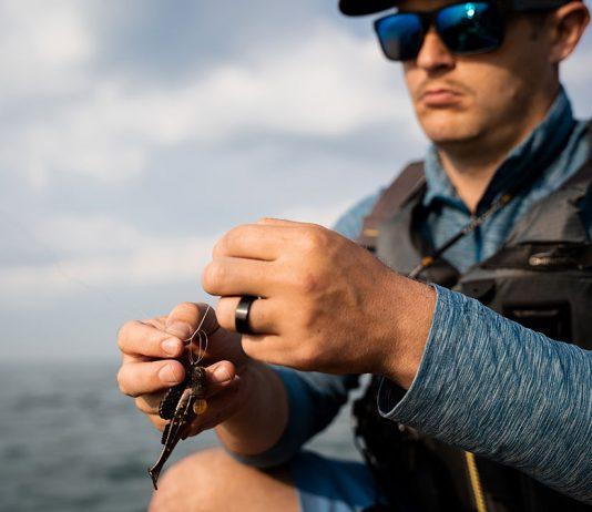 man ties his best fishing knot in a kayak