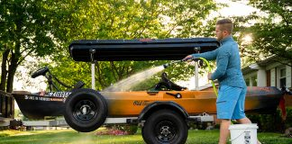 man washes his kayak outdoors as part of a care and maintenance routine