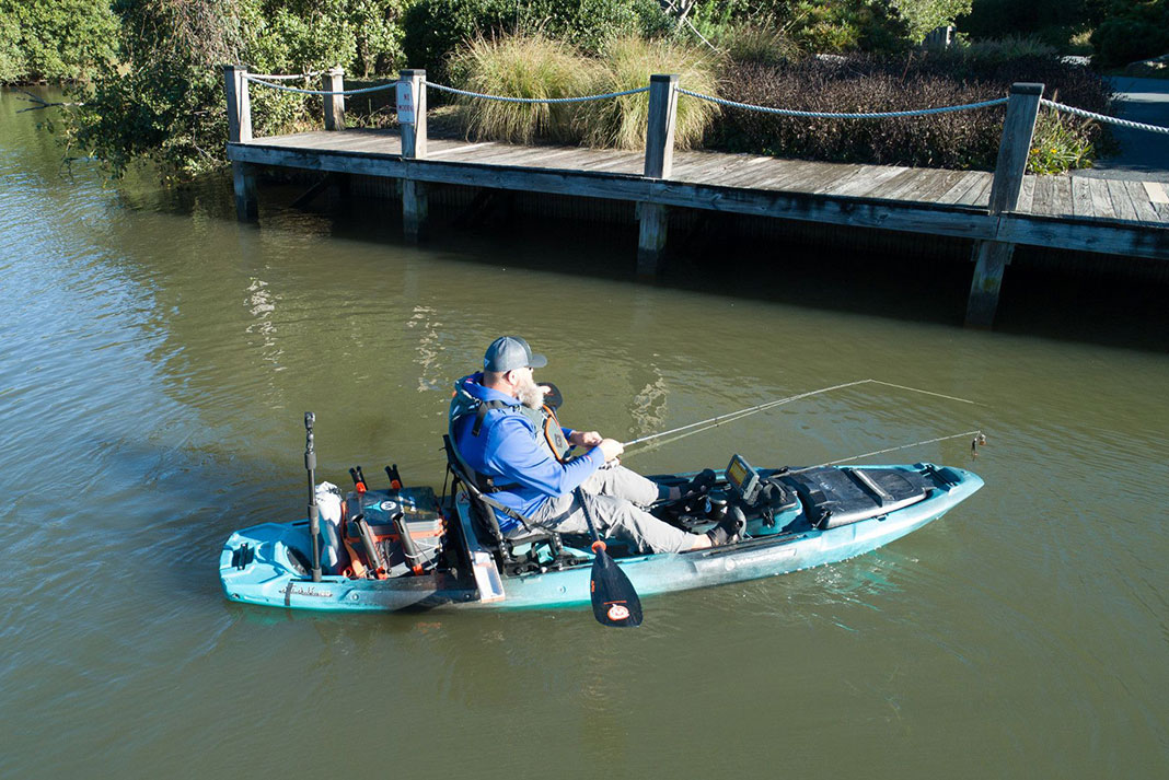 man fishes from a kayak under a dock using dock shooting technique