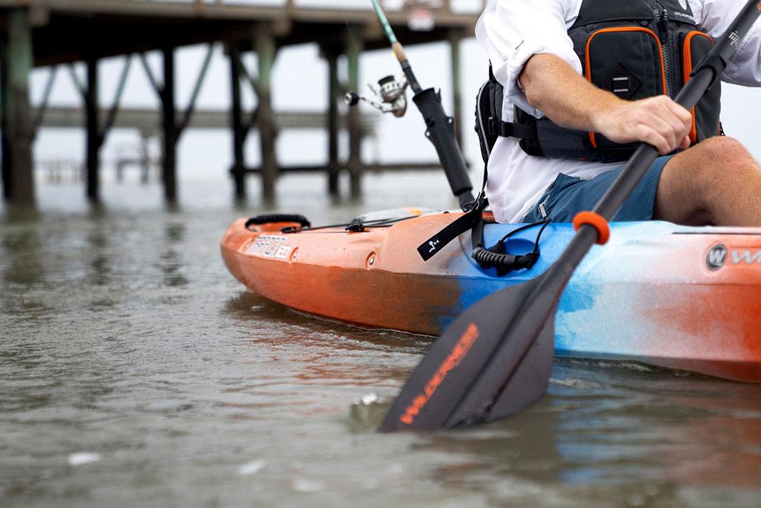angler paddles his kayak toward a pier