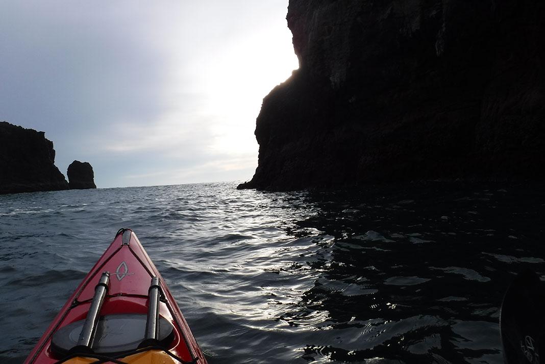 sea kayak navigates between two rock walls