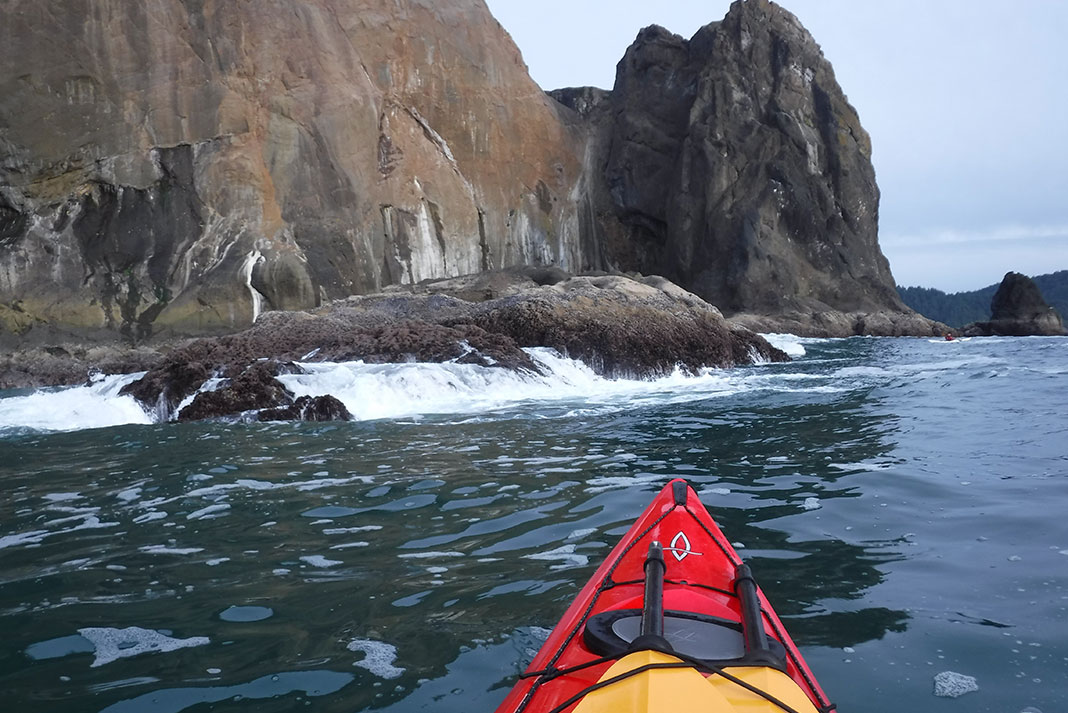 sea kayak approaches wave-washed rocks