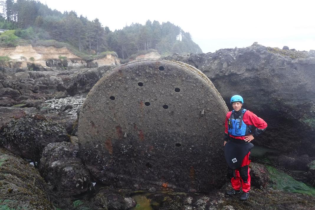 man stands beside sunken boiler on the Oregon coast