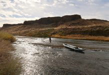 angler uses an inflatable tandem kayak to fish a low water fall river