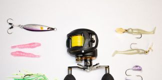 A selection of saltwater fishing lures and a reel laid out on a white background