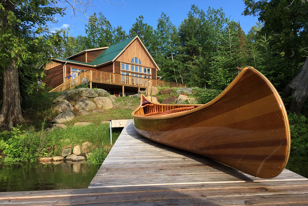 Rapid Media office on the Madawaska River with a wooden canoe on the dock