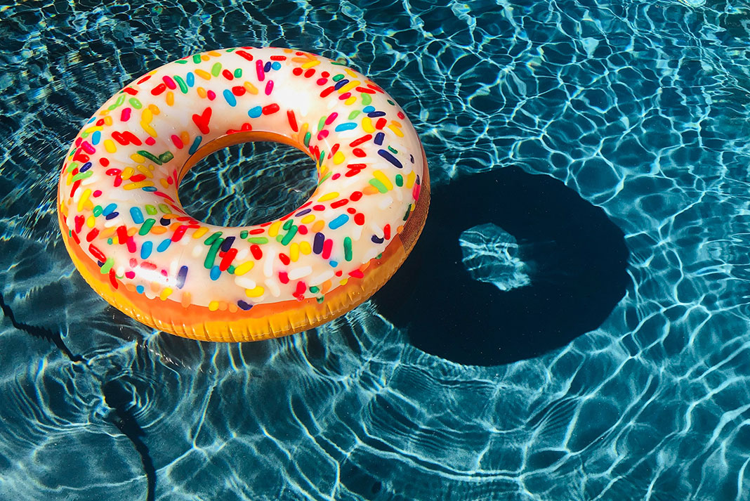 at inflatable tube decorated like a sprinkled donut floats in a pool