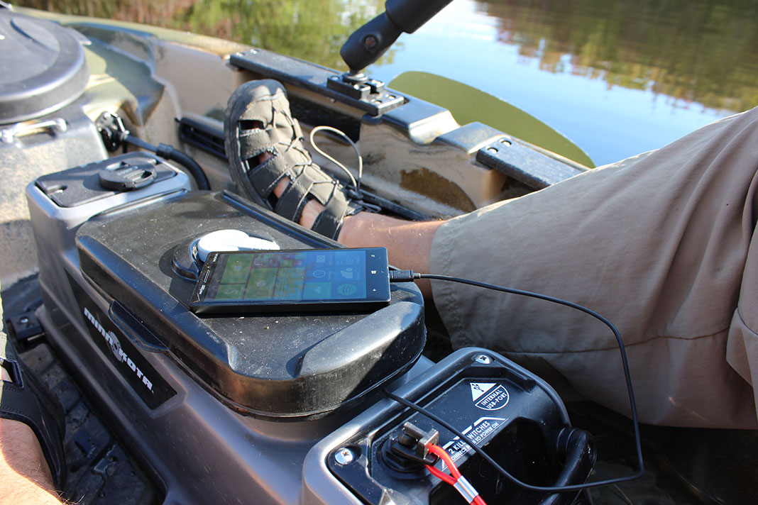 a cell phone plugged into a power source on a kayak