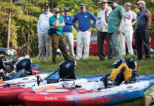 kayak anglers gather the shore to look at their fishing kayaks