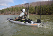 Person on a fishing kayak converted to a motor/pedal drive